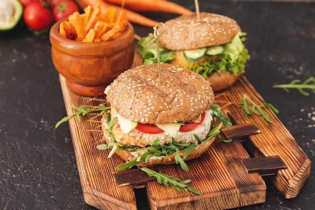 Deska ze smacznymi wegańskimi burgerami na ciemnym stole
