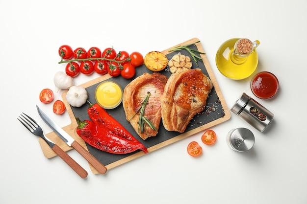 Deska ze smażonymi stekami i składniki do gotowania, widok z góry
