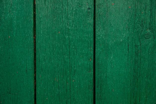 Deski drewniane malowane na kolor zielony. szorstka i popękana powierzchnia. stare drewno i farba.