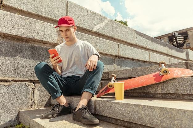 Deskorolkarz przygotowuje się do jazdy na ulicy miasta w słoneczny dzień. młody człowiek w trampkach i czapce z longboardem na asfalcie. pojęcie rekreacji, sportu, ekstremalnych, hobby i ruchu.
