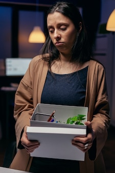 Desperackie uczucie zwolnienia ze stresu związanego z utratą pracy w miejscu pracy. smutna kobieta trzyma swoje rzeczy późno w nocy w biurze po zwolnieniu z pracy. zwolniona bizneswoman, kryzys gospodarczy