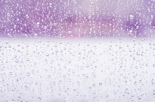 Deszcz krople i zamarznięta woda na nadokiennego szkła tle, purpurowy tonowanie