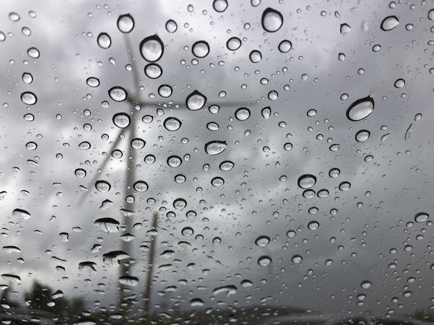 Deszcz na szybie samochodu na zewnątrz widać wiatrak. smutne i samotne tło
