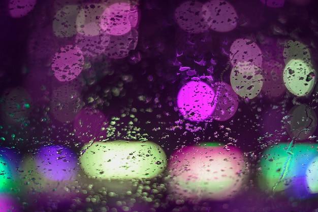 Deszcz obrazu spada na szybę samochodu, miasto zaświeca nocą w tle abstrakcyjnego boga. płytka głębia ostrości, przyczepność, nieostrość