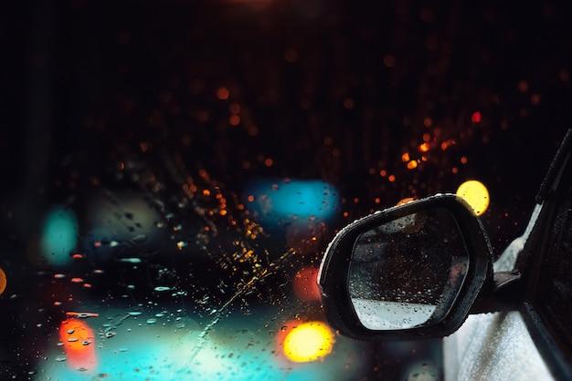 Deszcz opuszcza na szkle samochodowy okno z ulicznym bokeh przy nocą w pory deszczowa tle