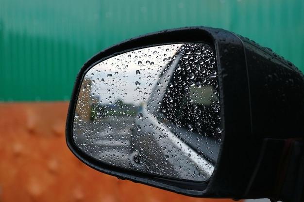 Deszcz spada na lusterko boczne samochodu w deszczowy dzień.