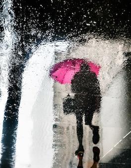 Deszcz w nowym jorku. odbicia od mokrych płyt. piesi spieszą się ze swoimi sprawami. rozmycie obrazu w ruchu