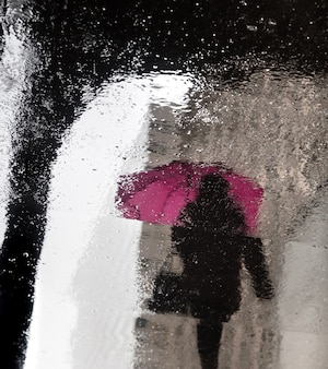 Deszcz w nowym jorku. odbicia od mokrych płyt. piesi spieszą się ze swoimi sprawami.