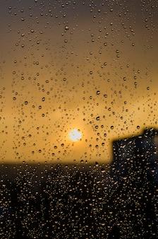 Deszcz za oknem na tle zachodu słońca. krople deszczu na szybie podczas deszczu. zachód słońca za oknem podczas deszczu. jasna tekstura kropli wody