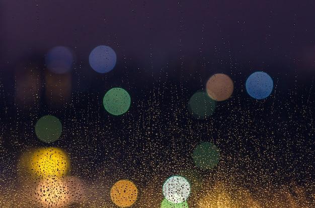 Deszczowa kropla na szklanym okno w sezonie monsunowym z kolorowymi bokeh światłami dla abstrakta i tła