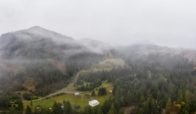 Deszczowa mglista i szara pogoda w górskiej dolinie karpat na ukrainie w małej wiosce