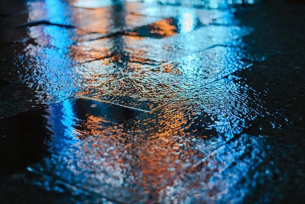 Deszczowa noc w dużym mieście, odbicia światła na mokrej nawierzchni drogi.