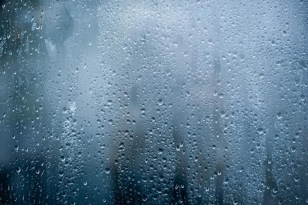 Deszczowe tło, krople wody deszczowej na oknie lub w kabinie prysznicowej, tło jesieni.