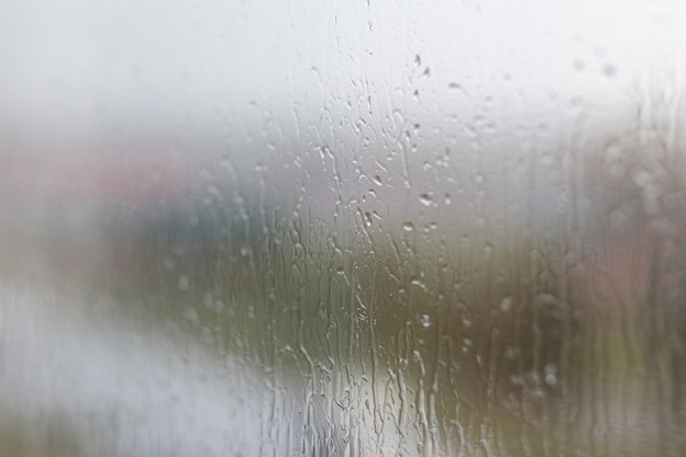 Deszczowy dzień przez okno na zachmurzony szary niebo i budynki miasta. pojęcie. wieczorny pejzaż miejski za szklanym oknem ze spływającymi kroplami wody.