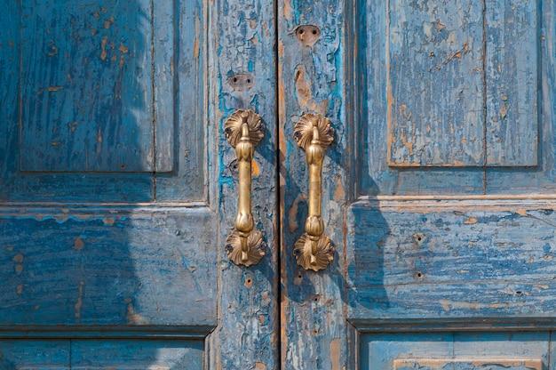 Detal architektoniczny z mosiężnej klamki w stylu vintage, zabytkowej klamki na starych niebieskich drzwiach drewnianych