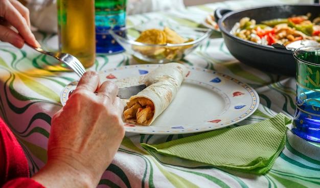 Detal kobiety toczącej meksykańską fajita na talerzu