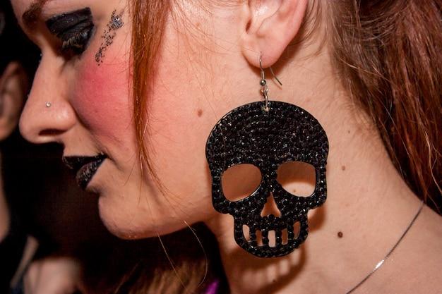Detal punkowej dziewczyny z kolczykiem w kształcie czaszki