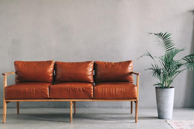 Detal wnętrza nowoczesnego salonu z brązową skórzaną sofą i roślinami domowymi.