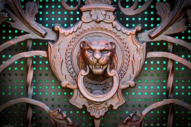 Detale, konstrukcja i ozdoby kutej bramy żelaznej. ozdoba dekoracyjna lwa, wykonana z metalu. vintage metaliczny wzór. elementy dekoracyjne jako tło.