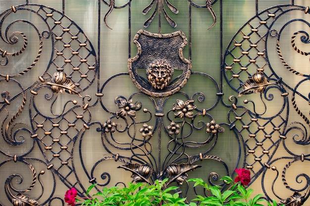 Detale, konstrukcja i ozdoby kutej bramy żelaznej. ozdobna ozdoba z lwami, wykonana z metalu.