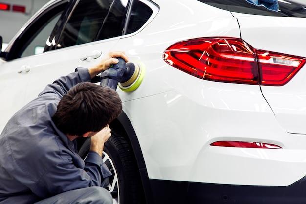 Detale samochodu - ręce z polerką orbitalną w warsztacie samochodowym