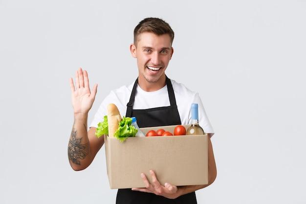 Detaliczna koncepcja zakupów spożywczych i dostawy przyjazny przystojny sprzedawca wykonany z pudeł...