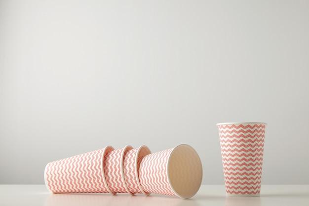 Detaliczny zestaw trzech papierowych kubków ozdobionych czerwonymi liniami i jednym stojącym obok na białym stole