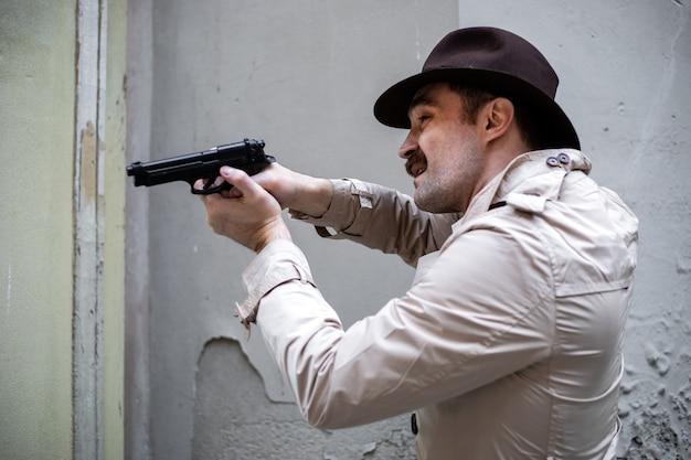 Detektyw kryjący się i celujący z pistoletu