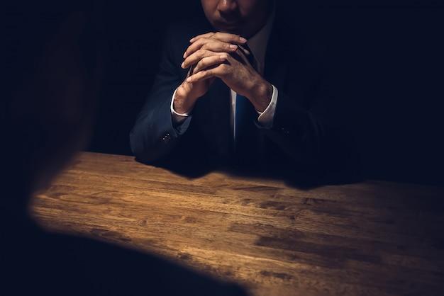 Detektyw przesłuchuje podejrzanego w ciemnym pokoju prywatnym
