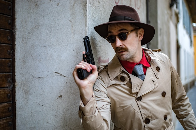 Detektyw przykrywający i celujący pistoletem
