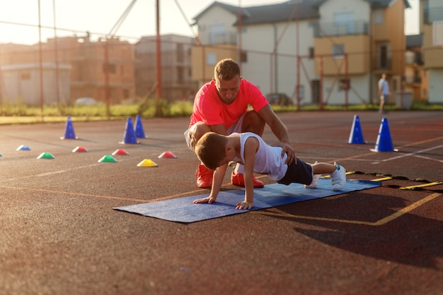 Determinacyjny młody trener piłkarski uczy małego chłopca, jak robić pompki.