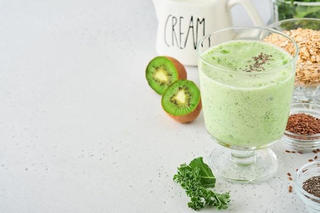 Detox green smoothie z jarmużem, szpinakiem i kiwi na jasnoszarym tle łupkowym, kamiennym lub betonowym. widok z góry z miejsca na kopię.