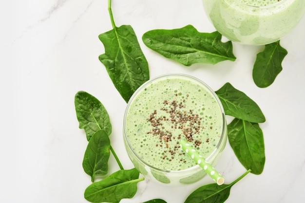 Detox green smoothie ze szpinakiem, nasionami chia i kiwi na jasnoszarym łupkowym, kamiennym lub betonowym stole. widok z góry