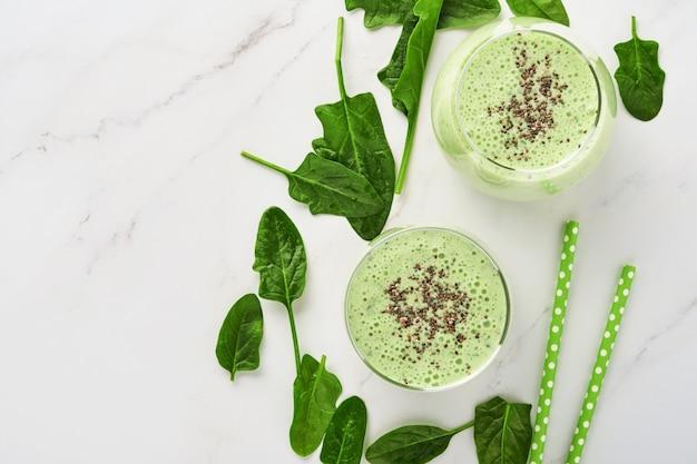 Detox green smoothie ze szpinakiem, nasionami chia i kiwi na jasnoszarym łupku, kamieniu lub betonie