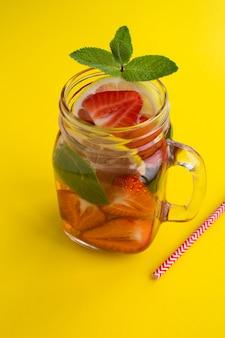 Detox lub infuzowana woda z truskawkami i cytryną w szklance. zbliżenie.