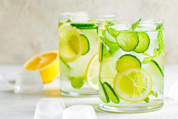 Detox sassy water z ogórkiem i cytryną w okularach, jasne tło. koncepcja zdrowego odżywiania.