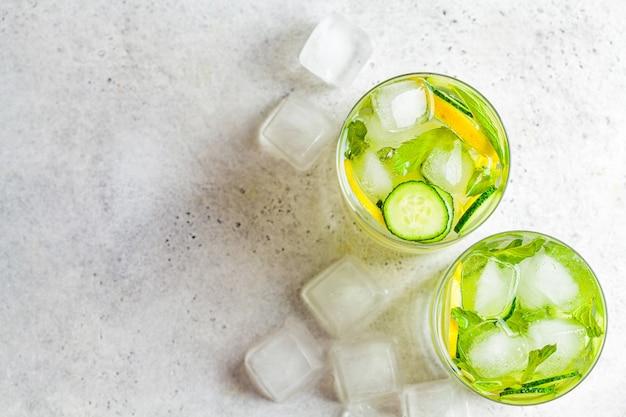 Detox sassy water z ogórkiem i cytryną w szkle, jasne tło, widok z góry. koncepcja zdrowego odżywiania.