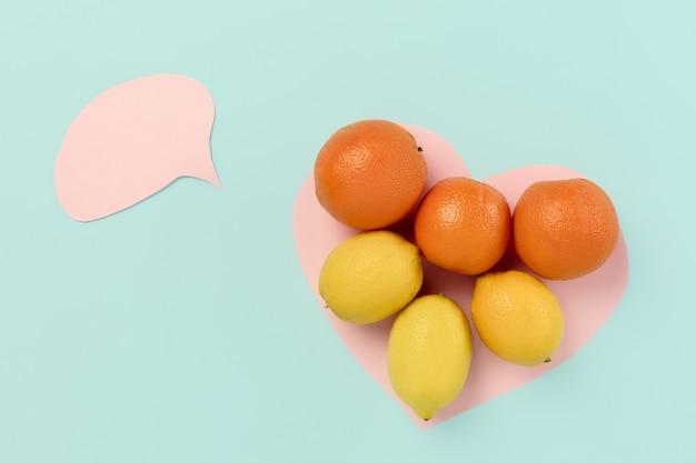 Detox super food wybór ze świeżych owoców w papierowym sercu na niebieskim tle. zdrowe odżywianie. koncepcyjna kompozycja z copyspace