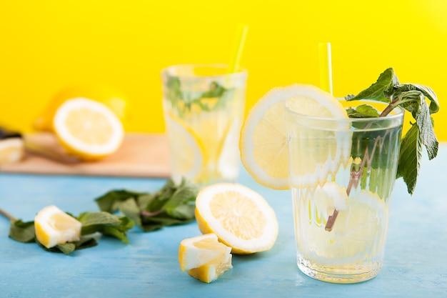 Detox woda cytrynowa w dwóch szklankach. delikatna domowa lemoniada