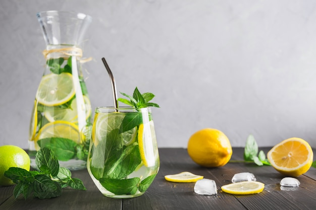 Detox woda lub lemoniada z miętą cytrynową, cytryny w szkle na drewnianym stole i szarym tle.