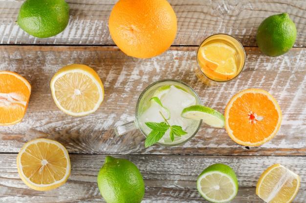 Detox woda z limonkami, cytrynami, pomarańczami, miętą w filiżance i szkłem na drewnianej powierzchni, płasko ułożona.