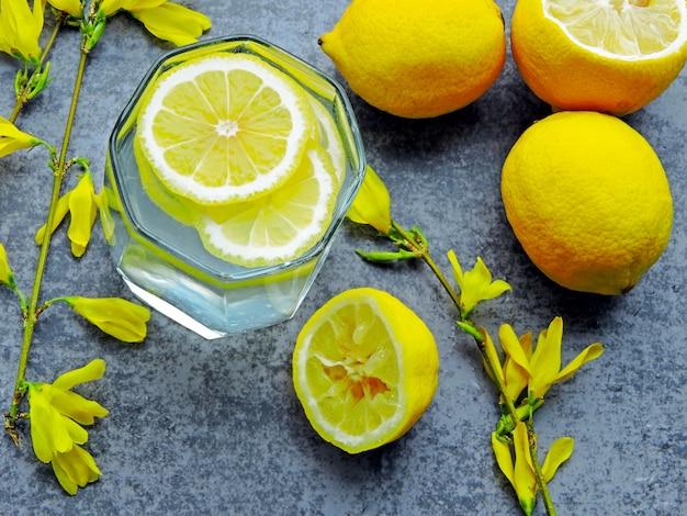 Detox woda z sokiem z cytryny i żółte kwiaty na gałęziach.