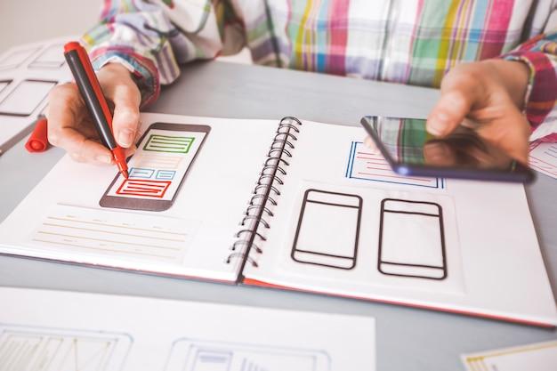 Deweloper opracowuje interfejsy użytkownika do aplikacji na telefon komórkowy.