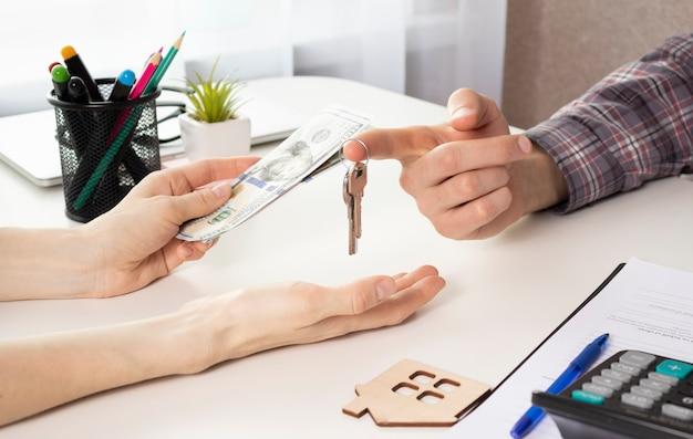 Deweloperzy domów i klienci uściskają rękę po zakończeniu zakupu lub wynajmu nieruchomości w celu przeniesienia prawa własności
