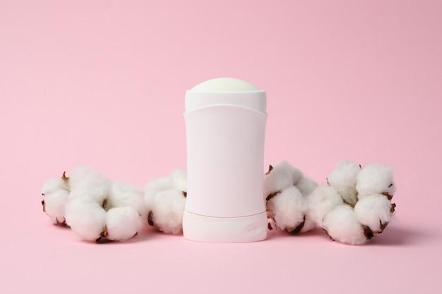Dezodorant do ciała i bawełna na różowym tle, puste miejsce na tekst