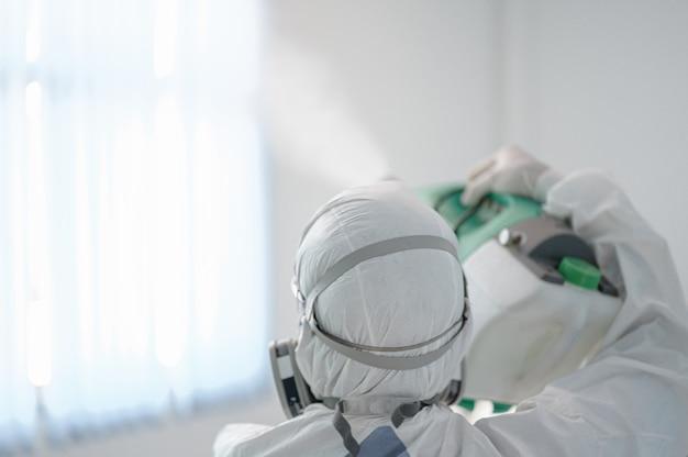 Dezynfekcja biura w celu zapobiegania covid-19, osoba w białym skafandrze przeciwdeszczowym z dezynfekcją w biurze, koncepcja koronawirusa