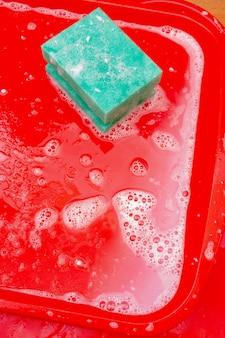 Dezynfekcja czerwonej plastikowej tacki na żywność w fast foodach. mycie tacki gąbką i mydłem.