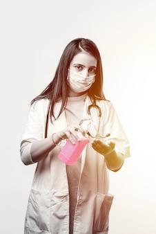 Dezynfekcja i mycie rąk - hinduska lekarka w mundurze i masce na twarz nakłada na ręce środek dezynfekujący lub odkażający. ochrona przed koronawirusem covid-19