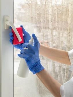 Dezynfekcja koronawirusem. ludzie w dezynfekcji okien. lekarz w gumowych rękawiczkach dezynfekuje klamkę okna środkiem dezynfekującym i gąbkami