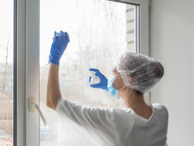 Dezynfekcja koronawirusem. ludzie w dezynfekcji okien. lekarz w gumowych rękawiczkach dezynfekuje okna środkiem dezynfekującym i gąbkami